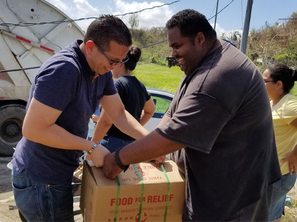 Rolando Flores delivers boxes of canned chicken to Pastor Walter Montañés of Vega Baja Mennonite Church.