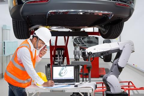 An automotive electrician stands in front of a car on a jack, working beside a robot